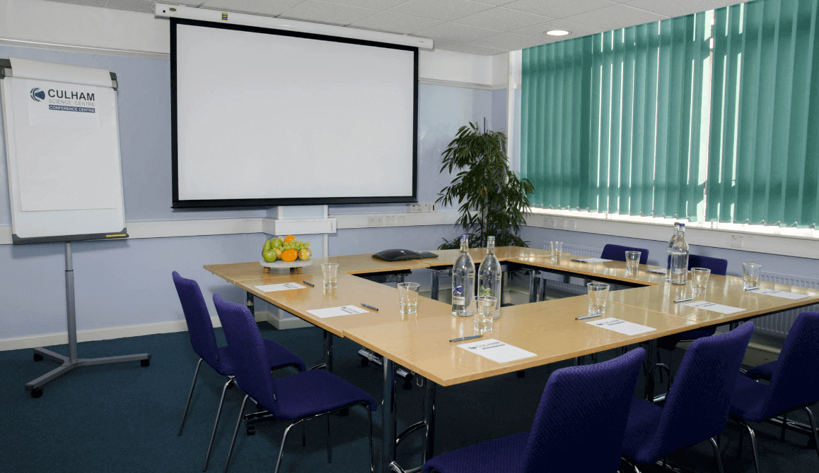 A meeting room with blue chairs and projector screen